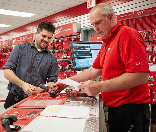 Two men at check out counter looking at tools